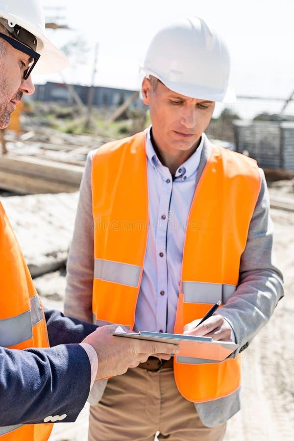 写在剪贴板的工程师在建造场所 免版税库存照片