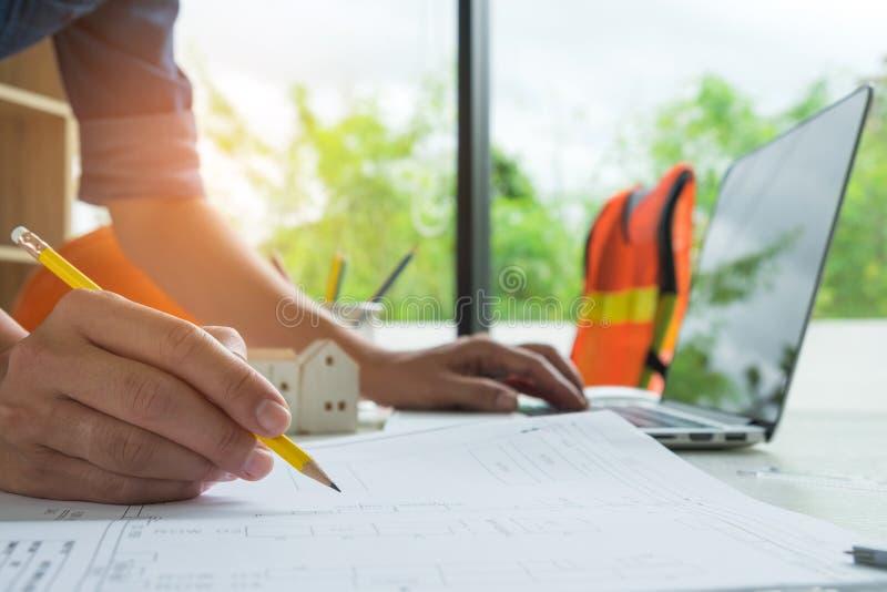 写在家设计和使用膝上型计算机,式样房子的建筑师  库存图片