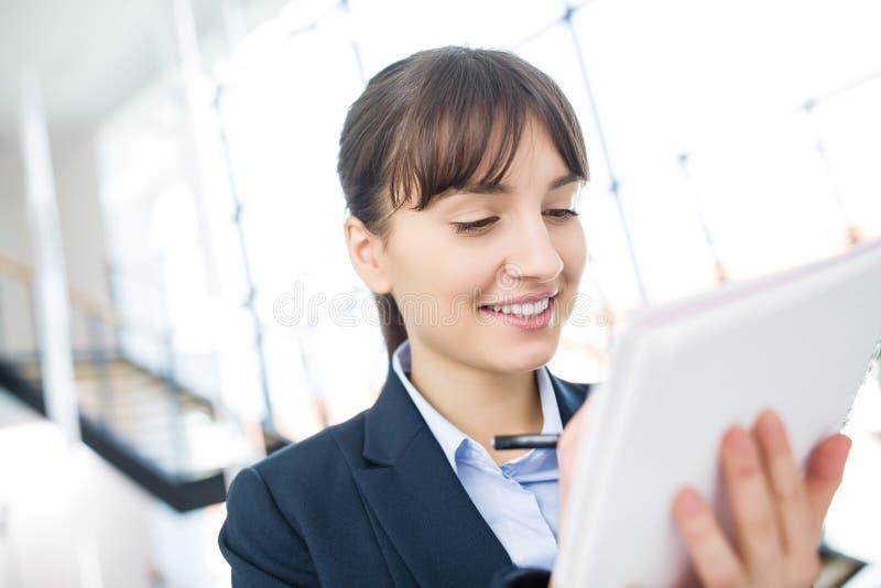 写在文件的微笑的女实业家在办公室 免版税库存图片