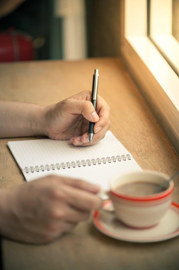 写在有咖啡杯的笔记本 图库摄影