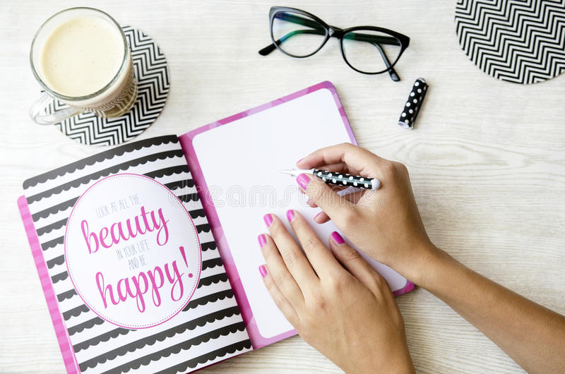 写在有行情的笔记本的女性手在木桌用冰冻咖啡和玻璃 免版税库存图片