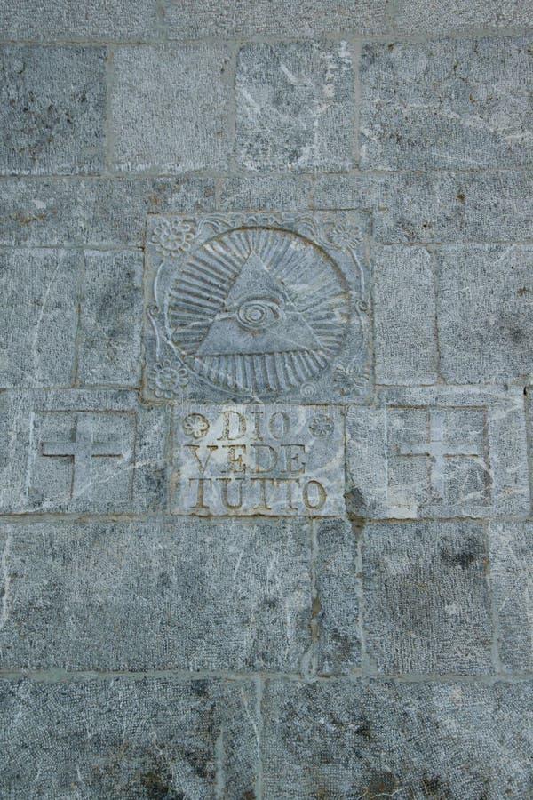 写在石墙`戴奥vede tutto `/`上帝看见一切上面`和共济会的标志 免版税库存照片