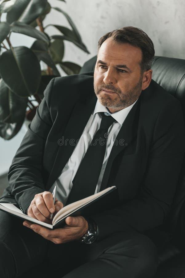 写在笔记本的周道的成熟商人,当坐时 免版税库存照片