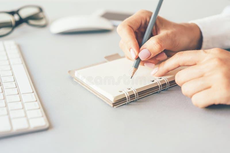 写在笔记本的女性手 免版税图库摄影