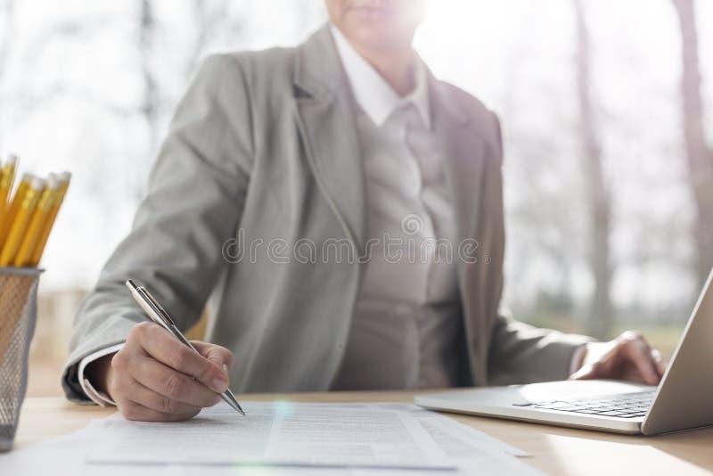 写在纸的成熟女实业家的中央部位,当坐与膝上型计算机在书桌反对窗口在办公室时 免版税库存图片