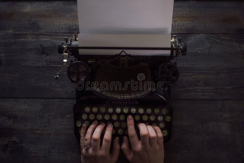 写在葡萄酒打字机的人的手 免版税库存照片