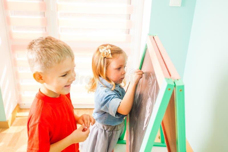 写在黑板的愉快的孩子在幼儿园 免版税库存图片