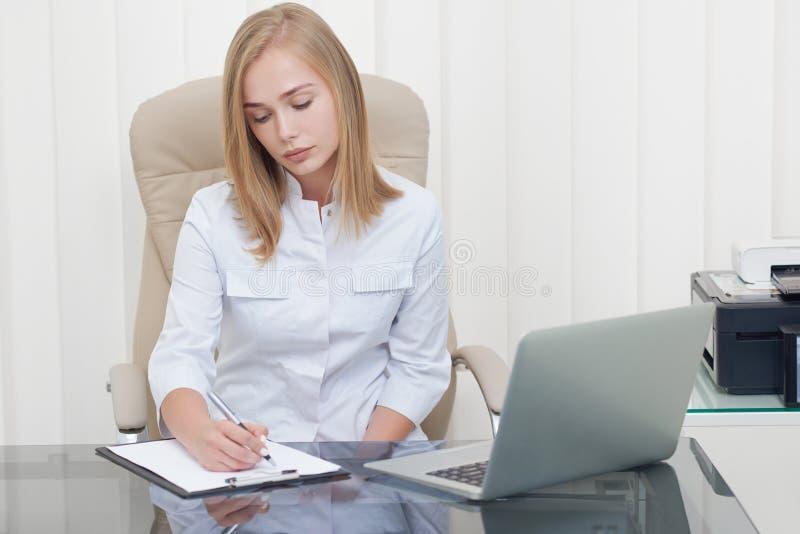 写处方的可爱的女性医生在诊所 库存图片