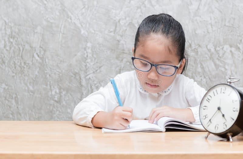 写她家庭作业在桌,教育的逗人喜爱的亚裔女学生 免版税库存照片