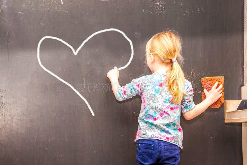 写心脏的逗人喜爱的小女孩在黑板 免版税库存图片