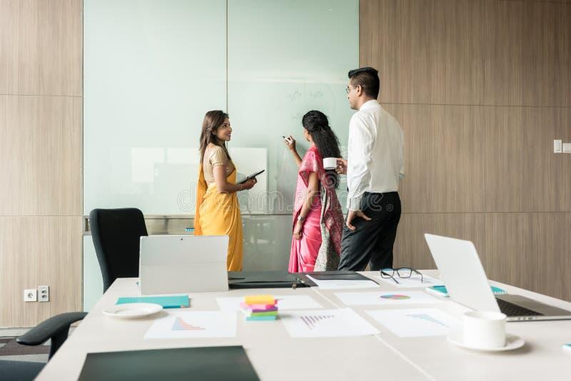 写想法的三个印地安同事在激发灵感期间 库存照片