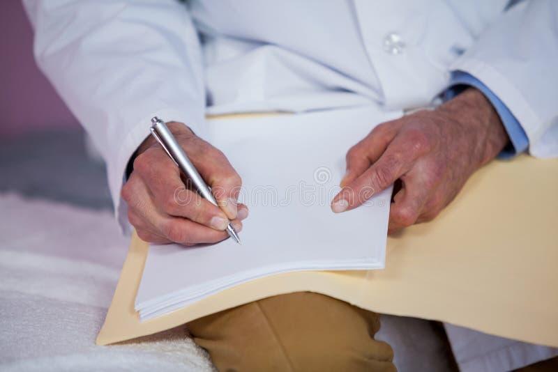 写报告的生理治疗师的中间部分 免版税库存图片