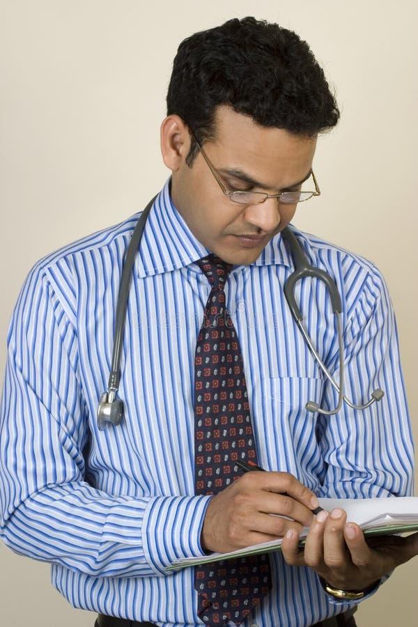 写报表的亚裔印第安医生 免版税库存图片