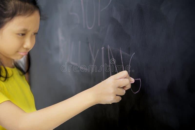 写文本中止胁迫的哀伤的矮小的女小学生 库存照片