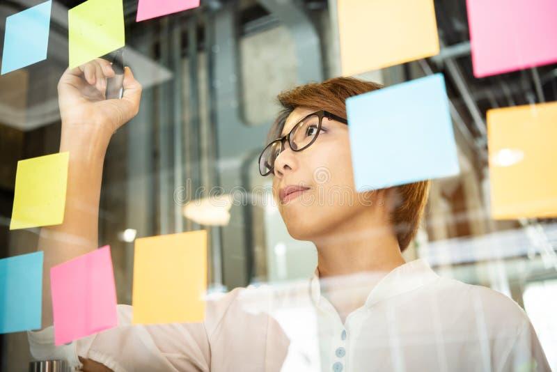 写新的想法的年轻女人设计师在稠粘的笔记 库存照片