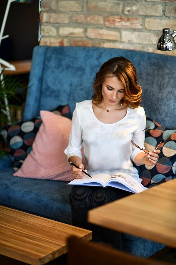 写未来规划和目标,放松在一个舒适餐厅读书的梦想的年轻美女在她的日志 免版税库存图片
