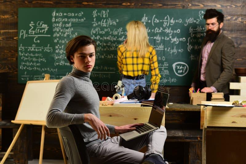 写某事的殷勤学生在他们的笔记本,当坐在书桌在教室时 学生是 库存照片