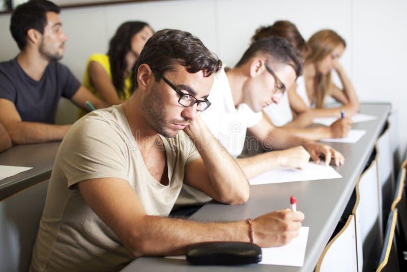 写检查的学生在教室 免版税库存照片