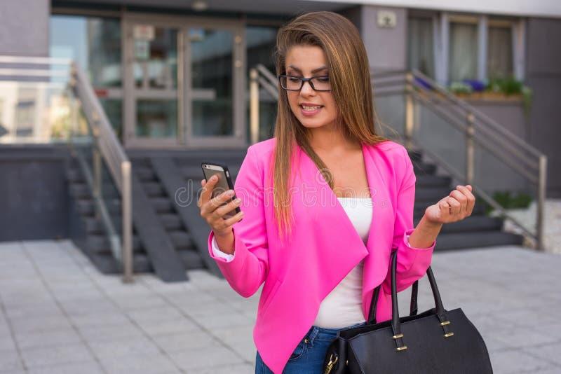 写消息的年轻美丽的女实业家在智能手机af 库存照片