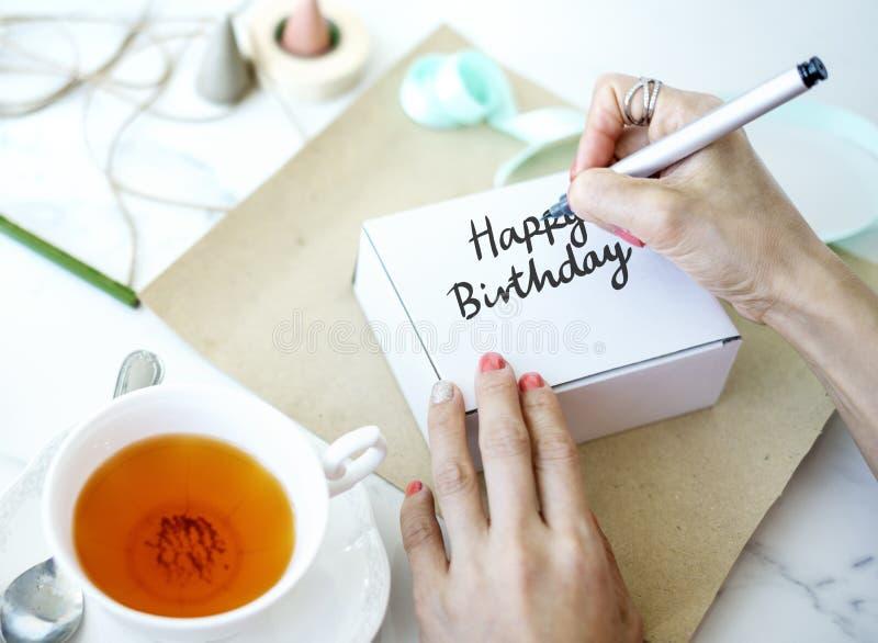 写生日快乐的妇女在白色箱子 库存图片