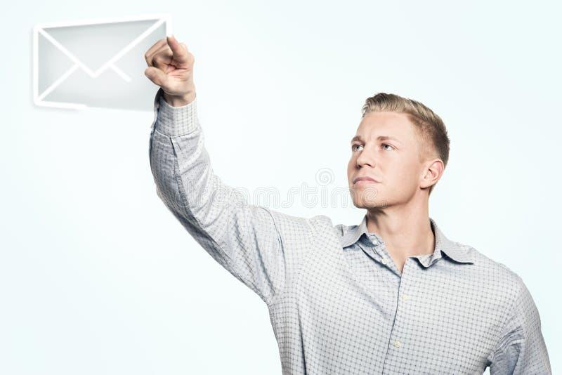 年轻商人在天空中的画电子邮件标志。 免版税库存照片