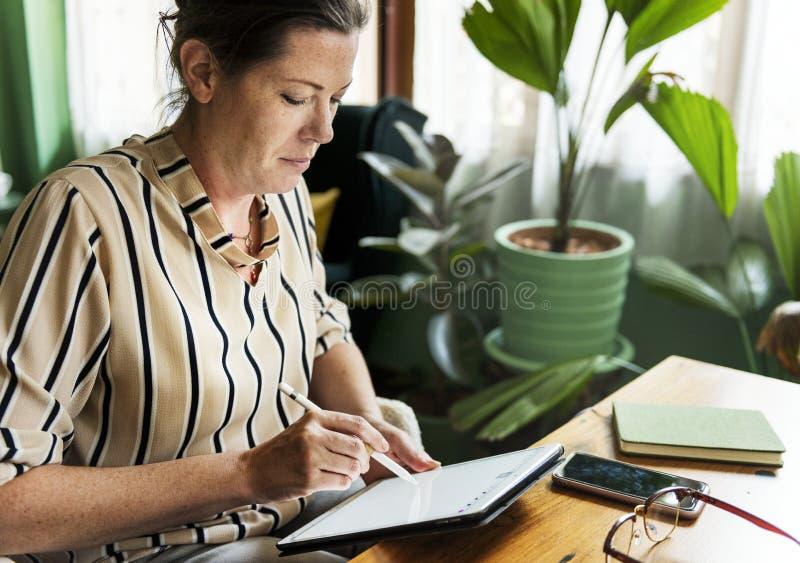写白种人的妇女做在片剂的名单 图库摄影
