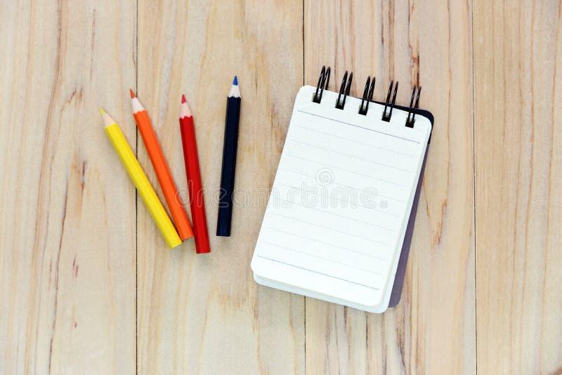 写的信息小笔记本纸笔记薄与颜色铅笔在木桌 图库摄影