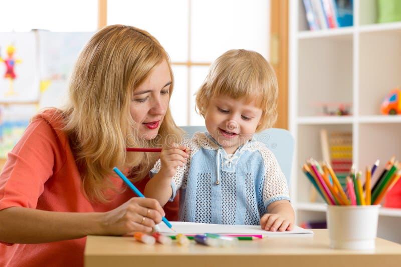 写的妇女教的孩子 与老师的基本的学生绘画 免版税库存图片