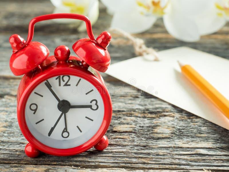 写的铅笔红色闹钟笔记薄在木土气桌 库存照片