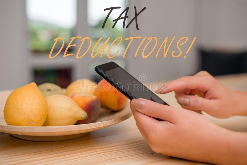写税收减免的手写文本 意味能被收税费用的减少收入的概念 免版税库存图片