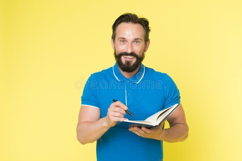 写笔记的人成熟有胡子的人给笔记薄 检查什么做 每日日程表 开发的习性和设定 免版税库存照片