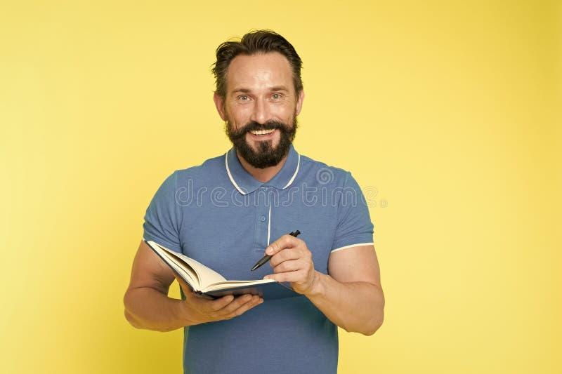 写笔记的人成熟有胡子的人给笔记薄 检查什么做 每日日程表 开发的习性和设定 库存照片