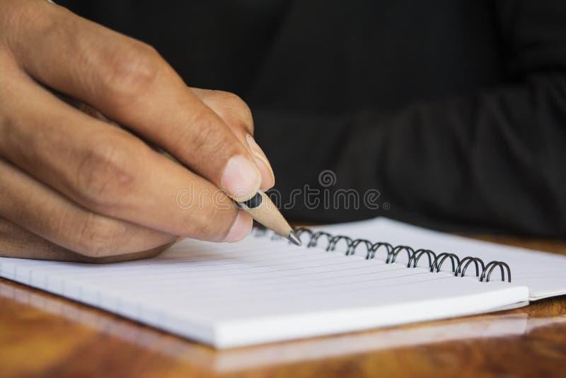写笔记的人的手 库存图片