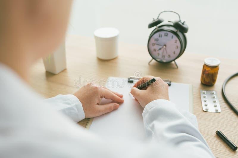 写笔记的女性医生在剪贴板纸在医疗前期间 免版税图库摄影