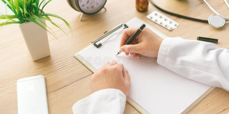 写笔记的女性医生在剪贴板纸在医疗前期间 库存照片