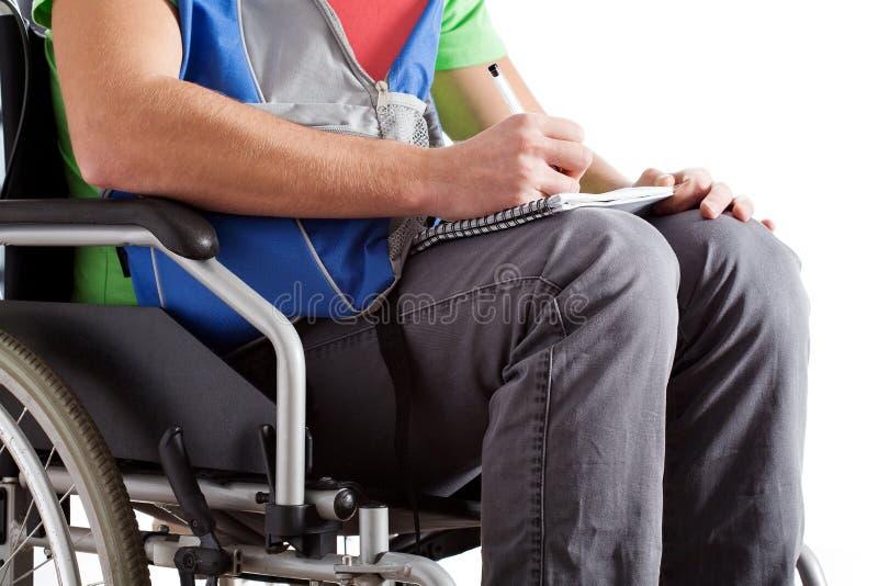 写笔记的残疾学生 免版税库存图片
