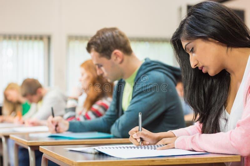 写笔记的年轻学生在教室 免版税库存图片