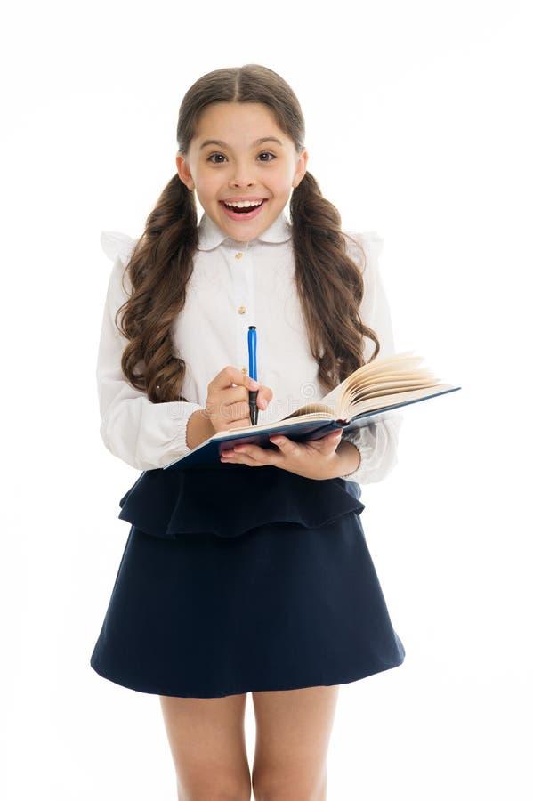 写笔记记住 愉快儿童校服聪明的孩子做笔记 儿童女孩愉快的校服给举行穿衣 库存图片