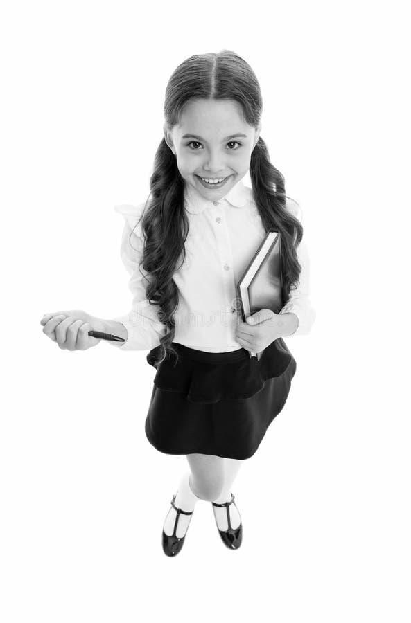 写笔记记住 愉快儿童校服聪明的孩子做笔记 儿童女孩愉快的校服给举行穿衣 免版税库存照片