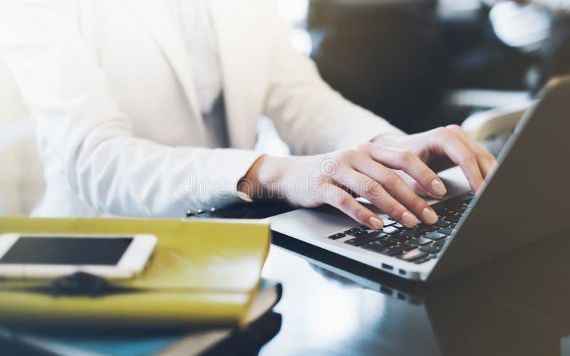 写粗体正楷的年轻女人在开放膝上型计算机在一张桌上的一个咖啡馆与反射和强光,工作在comp的女实业家 免版税图库摄影