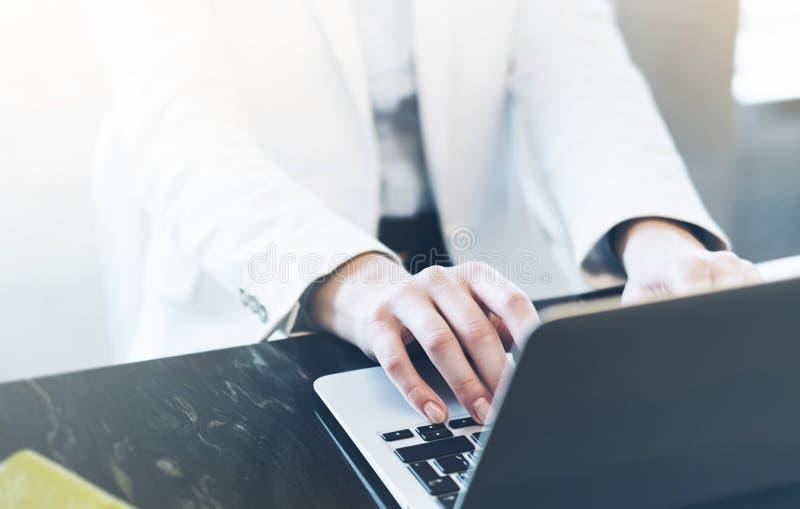写粗体正楷的年轻女人在开放膝上型计算机在一张桌上的一个咖啡馆与反射和强光,工作在comp的女实业家 免版税库存照片