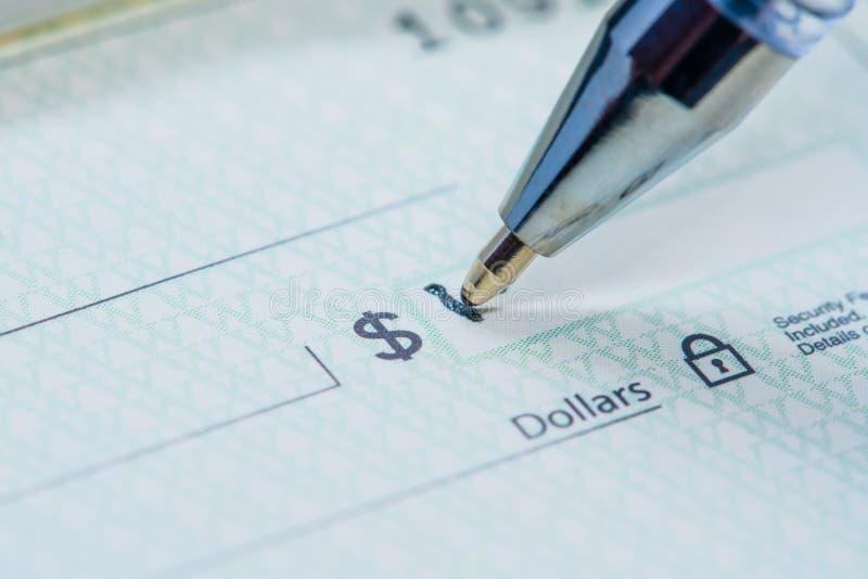 写美元数额的笔在检查 免版税库存照片