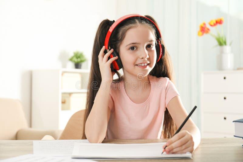 写音乐笔记的女孩在桌上 免版税库存照片