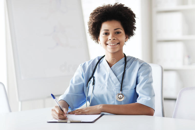 写给剪贴板的愉快的女性医生或护士 图库摄影