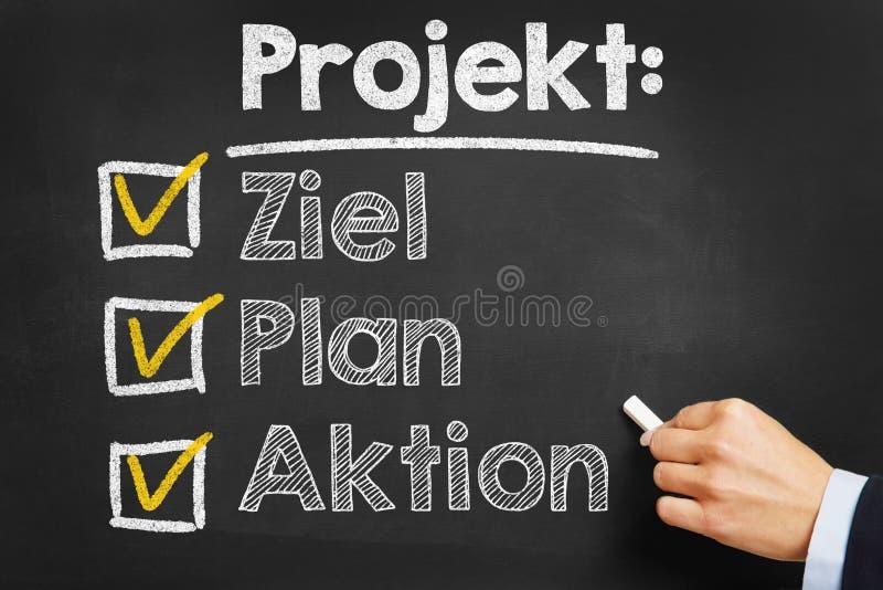 写Projekt的手:在黑板的Ziel计划Aktion 免版税库存照片