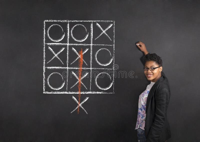 写tic TAC脚趾的南非或非裔美国人的妇女老师在白垩黑色委员会背景 免版税库存照片