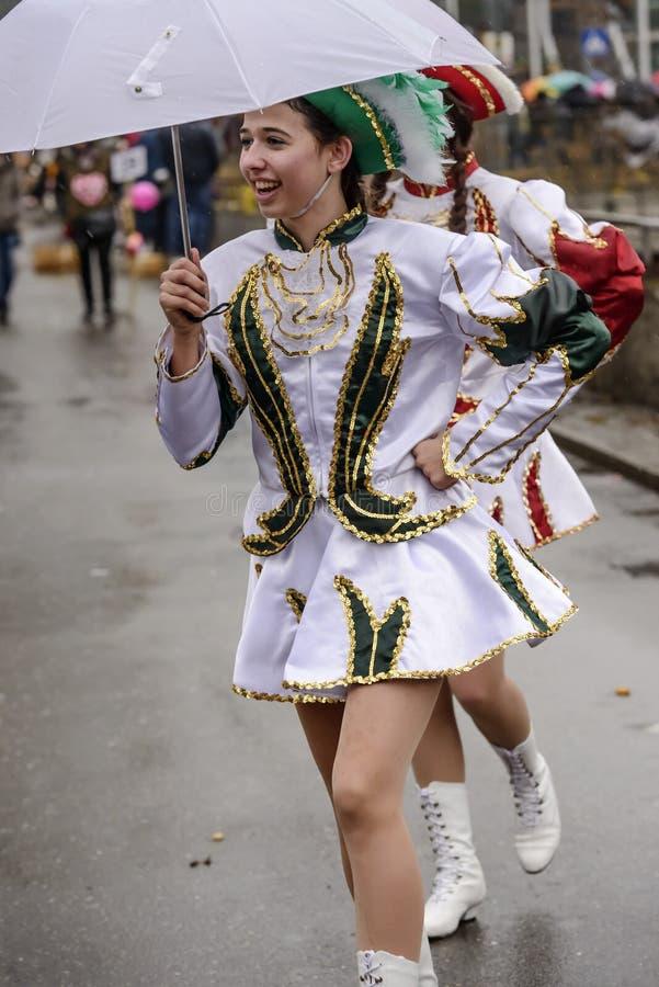 年轻军乐队女队长微笑在白色伞下对狂欢节队伍, 免版税图库摄影