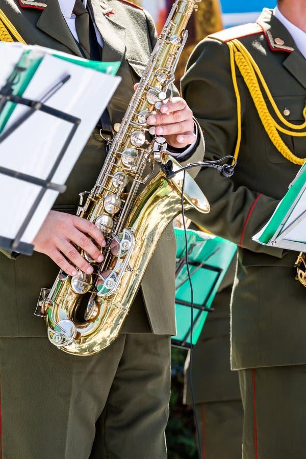 军事乐队的音乐家弹萨克斯管 免版税库存图片
