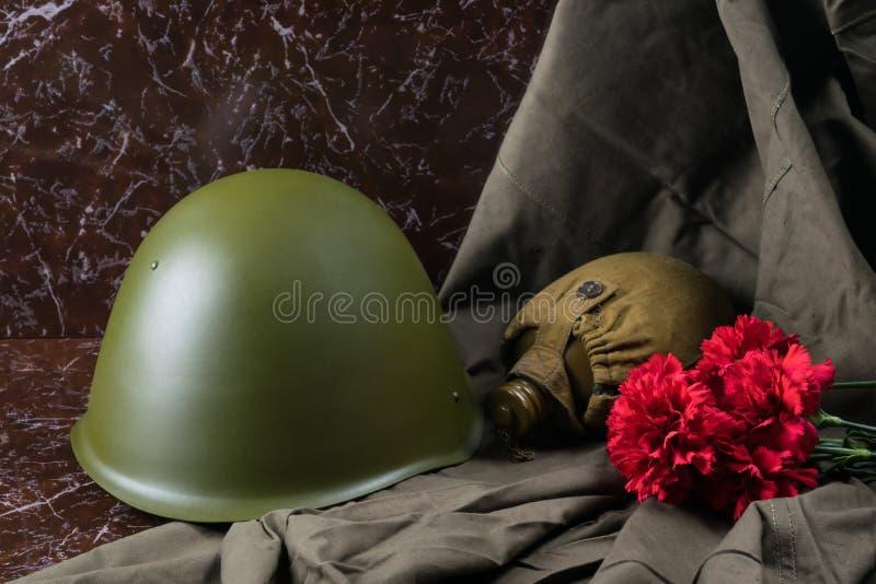 军事事和红色花在一块大理石平板,争斗的纪念碑 免版税图库摄影