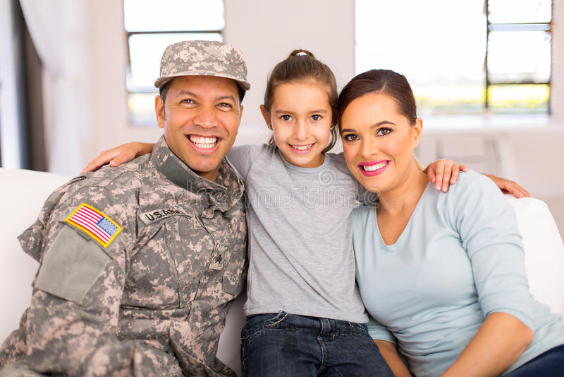 军事家庭坐的长沙发 库存图片
